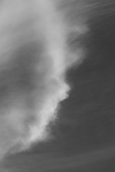 Natural art created by clouds like cotton wool against a blue sky depicted in black and white.