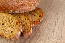 Natural background.Beautiful slices of cereal bread on a wooden surface.Top view on slices of bread.Texture of cereal bread.Abstract textured background.Close-up, horizontal, cropped shot, top view.