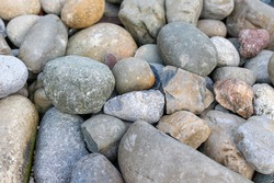Natural background of a big rocks or pebbles on the seashore close-up. The surface of the beach on the ocean is covered with large polished round stones of gray color of different sizes.