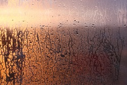 Natural background of condensation of water on a window glass with high air humidity, large drops dripping. Natural sunlight through glass. High humidity