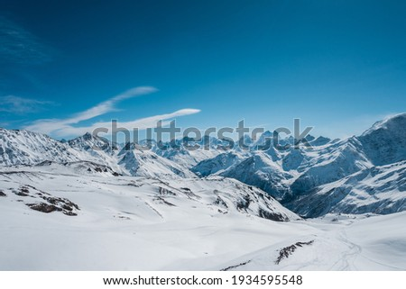Natural background. Panorama of the peaks of the Caucasus Mountains with glaciers and snow.