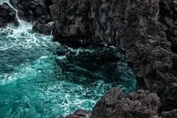 natural background. seawater naturally breaking on the strong volcanic rocks. tidewater green ocean water flow to the dark grey and black rocks. texture background and free space for designers.