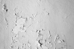 Natural background. Wall with a shabby and peeling paint and plaster. Contrast and volume, white, gray.