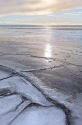 Natural background with freezing-over sea bay at a frosty sunrise. Change of seasons. Beautiful landscape. Freezing Baikal Lake