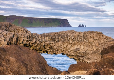 Natural basalt arch at Dyrholaey promontory near the village of Vik i Myrdal, a popular tourist attraction on the South Coast of Iceland, with Reynisdrangar basalt sea stacks seen in background