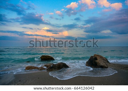 Natural beach with rocks. Clouds in the sunset.