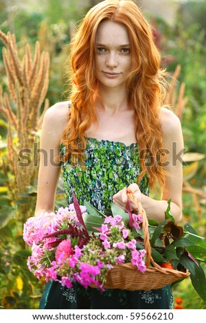 Natural beautiful red-haired girl holds on hands basket with garden flowers