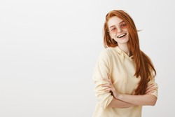 Natural beauty always the best. Indoor shot of creative good-looking european girl with red hair wearing trendy glasses and stylish yellow hoodie, smiling broadly, half-turned with crossed hands