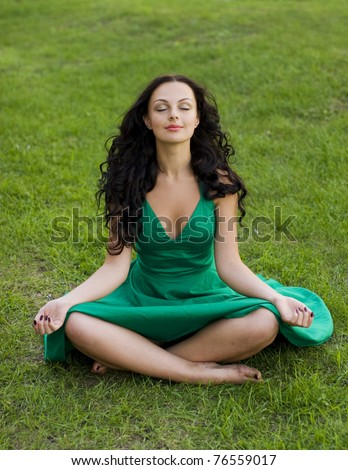natural beauty brunette girl in green dress sit on the grass
