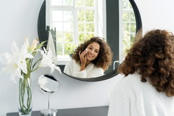 Natural beauty concept. Glad young afro american woman making morning routine, removing makeup, looking at mirror, holding cotton pad in hands near face and sitting in bathrobe at bathroom