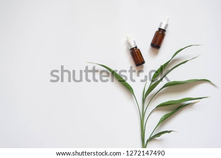 Natural beauty cosmetic product for skincare concept. Brown glass vial w/ dropper and organic green leaves on white background. Serum or essential oil w/ herbal extract. Branding mock-up. Copy space. #1272147490