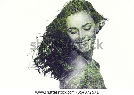 Natural beauty. Digitally composed portrait of beautiful young woman keeping eyes closed and smiling over a picture of green forest