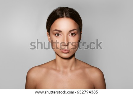 Natural beauty. Portrait of a brunette woman looking at the camera while standing on a white background