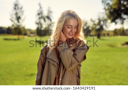 Natural beauty. Portrait of young and attractive woman in beige cloak smiling and enjoying time in the park. Nature concept. Beautiful people