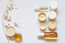 Natural bio cosmetics with oats milk and honey for body and face care: creams, gels, soaps, spray on a white background. Organic cosmetic products. Flat lay, top view, copy space, close up