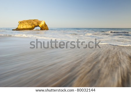 Natural Bridges rock in the Beach of Santa Cruz, California, USA. With ocean wave in the foreground.