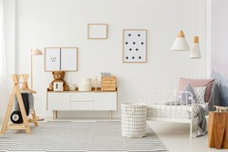 Natural, bright kid's bedroom interior with wooden furniture, designer accessories and posters on a white wall