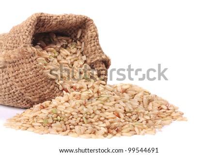 Natural brown rice in small burlap sack - stock photo