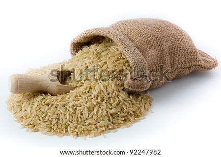 Natural brown rice in small burlap sack and wooden spoon