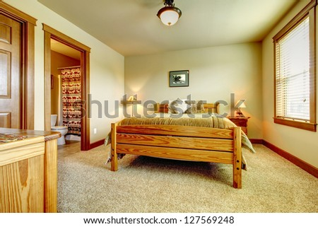 Natural cabin farm house bedroom with beige carpet and green walls.