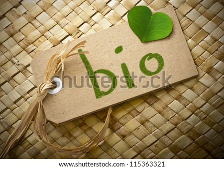 Natural cardboard label with the word bio handwritten on it plus a green clover petal