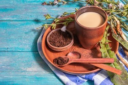 Natural chicory coffee with fresh flowers and powder. Caffeine-free drink in a ceramic glass. Alternative replacement for coffee, caffeine. Turquoise wooden background, place for text
