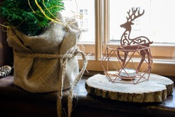 Natural christmas window decoration with handmade reindeer and trees of wood.