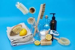 natural cleaning stuff, sustainability and eco living concept - lemon halves, washing soda, bottle of vinegar with laundry and liquid soap and brushes on blue background