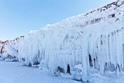 Natural cold background of icy coastal rocks with blue long icicles on a winter sunny day. Frozen Baikal Lake, Olkhon Island. Winter unusual landscape
