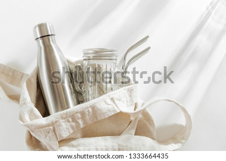 Natural color eco bag with reusable metal water bottle, glass jar and straw. Zero waste. Sustainable lifestyle concept.  #1333664435