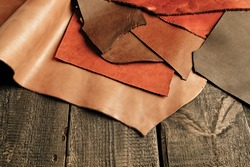 Natural color leather. Materials for leather craft. Copy space. Multi colored leather in rolls. Handmade craft. Different samples of leather on wooden table