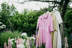 Natural colored dresses hanging on on a tree in the garden with lupine flowers. Concept organic clothes, eco-friendly, ecological fashion.