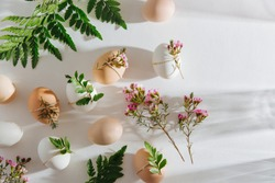 Natural Colored Eggs decorated with flowers in morning sunlights. Stylish minimal Compositions in pastel colors.  Easter concept.