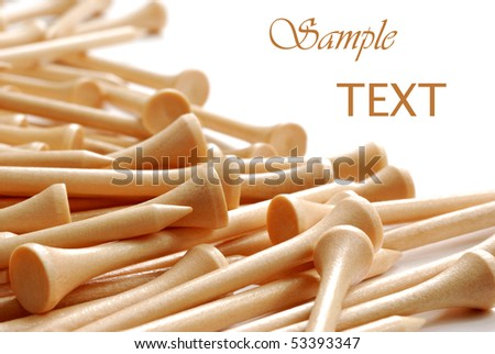 Natural colored wooden golf tees on white background with copy space.  Macro with shallow dof.