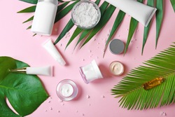 Natural cosmetics and leaves on pink background