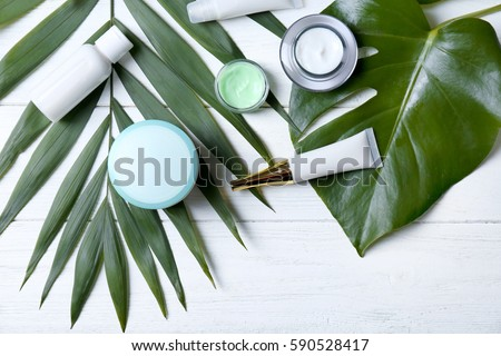 Natural cosmetics and leaves on table