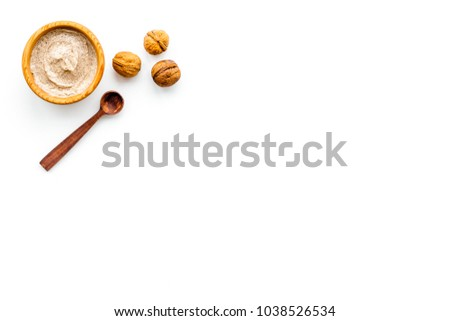 Natural cosmetics for skin care. Body scrub with walnut. White background top view copy space #1038526534