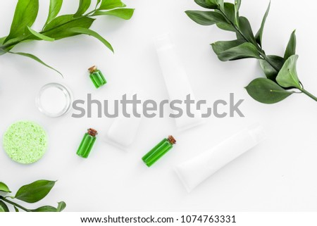 Natural cosmetics for skin care near green leaves on white background top view #1074763331