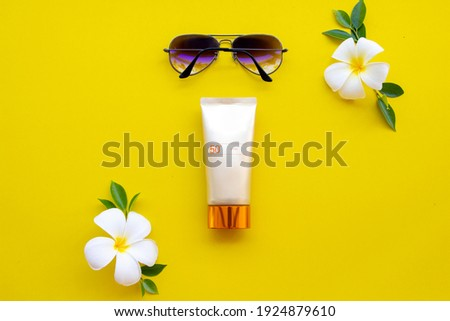 natural cosmetics sunscreen spf50 health care for skin face with sunglasses ,flowers frangipani of lifestyle woman relax in summer arrangement flat lay style on background yellow