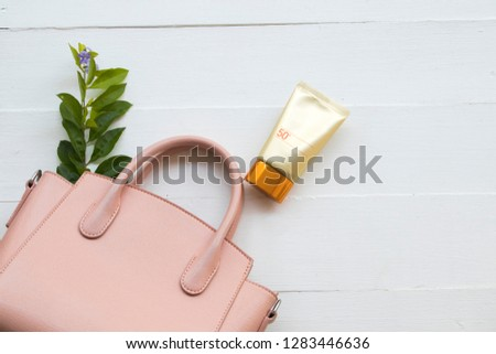 natural cosmetics sunscreen spf50  health care skin face and pink hand bag of lifestyle woman relax with purple flower decorate on background white
