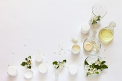 Natural cosmetics with floral apple extract. Jars of face and hand creams, soap and moisturizing gel on a laboratory table with chemical glassware. Creation of new types of cosmetics