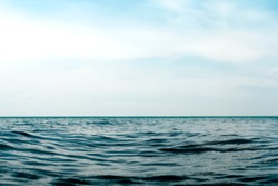Natural dark blue seawater surface with blue sky