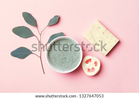 natural eco beauty products on pink background, luffa sponge, clay for making facial or body mask, handmade herbal and coconut soap and eucalyptus leaf, top view, copy space, flat layout