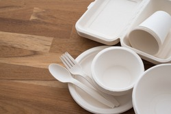 Natural eco-friendly disposable utensils (fork, spoon, dish plate, bowl, cup and fast food box container) made of fiber of bagasse and bamboo on wooden table background with copy space. Save the earth
