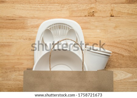 Natural eco-friendly disposable utensils (fork, spoon, dish plate, bowl, cup) in recycle paper bag made of fiber of bagasse and bamboo on wooden background. Save the earth, waste reduction concept. Foto stock ©