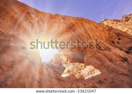 Natural erosive arch in hills from red sandstone in desert