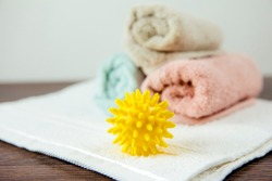 Natural fabric softener spiky dryer ball for more soft clothes while tumble drying concept.