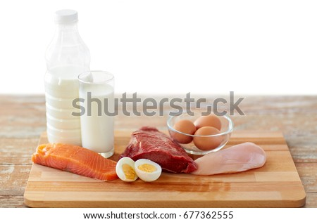 natural food, healthy eating and protein diet concept - raw meat fillet, fish, milk and eggs on wooden table