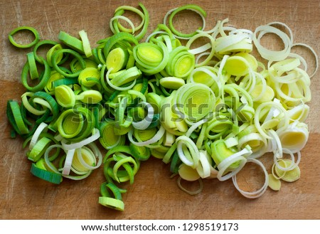 Natural fresh cutted leeks on the wooden cutting board. Leek cut by means rings on a chopping board. Closeup of sliced leek. Slices of the fresh green leek. Chopped Leek. Fresh vegetables. Top view. Сток-фото ©