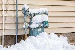 Natural gas meter covered in snow during winter. Concept of energy conservation, residential heating costs and natural gas production